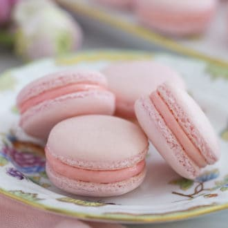 Four pink macarons on a porcelain plate.