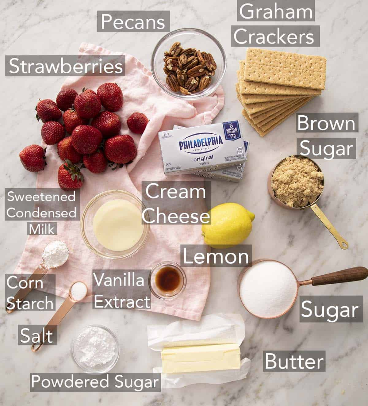 Ingredients for making a no bake strawberry cheesecake on a counter.