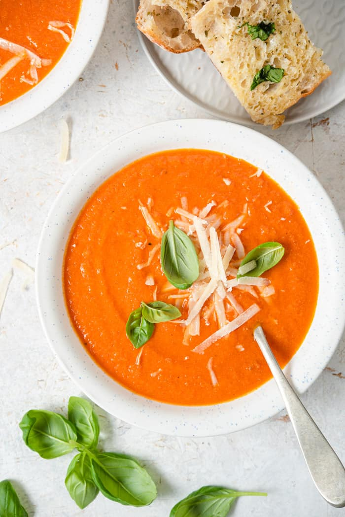 An overhead shot of tomato soup with basil, Parmesan and garlic bread