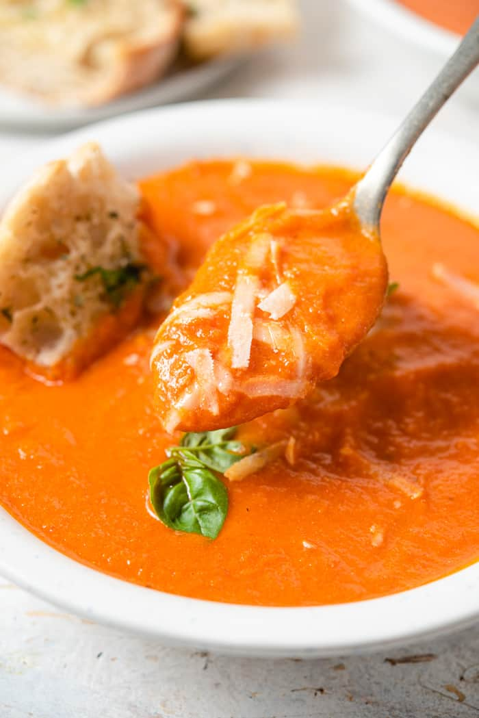 A close up of a spoonful of tomato soup