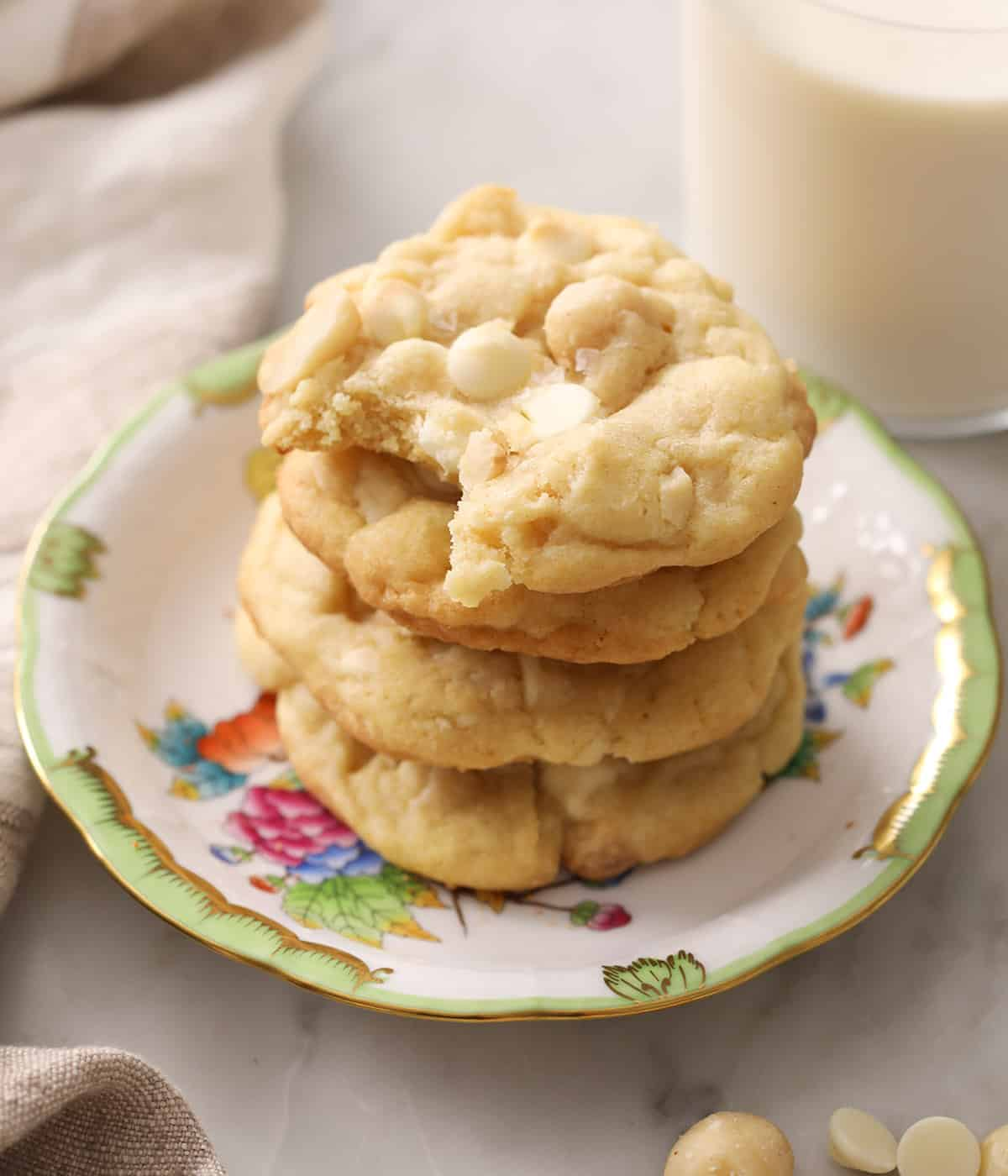 Two white chocolate macadamia nut cookies on a porcelain plate next to a glass of milk.