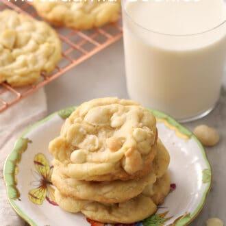 A glass of milk next to some white chocolate macadamia nut cookies