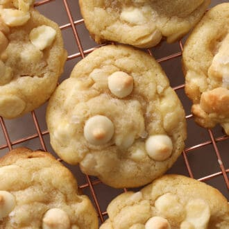 White chocolate chip macadamia nut cookies on a copper cooling rack