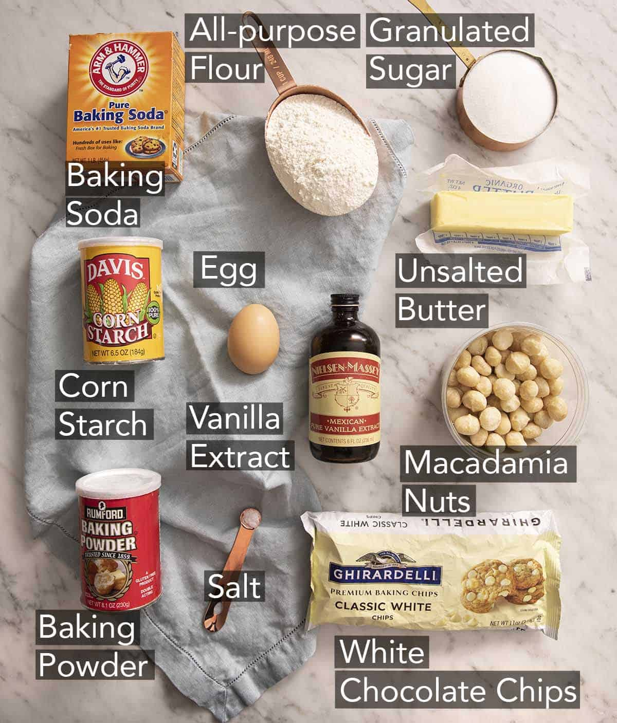 Ingredients to make white chocolate chip macadamia nut cookies on a marble counter.