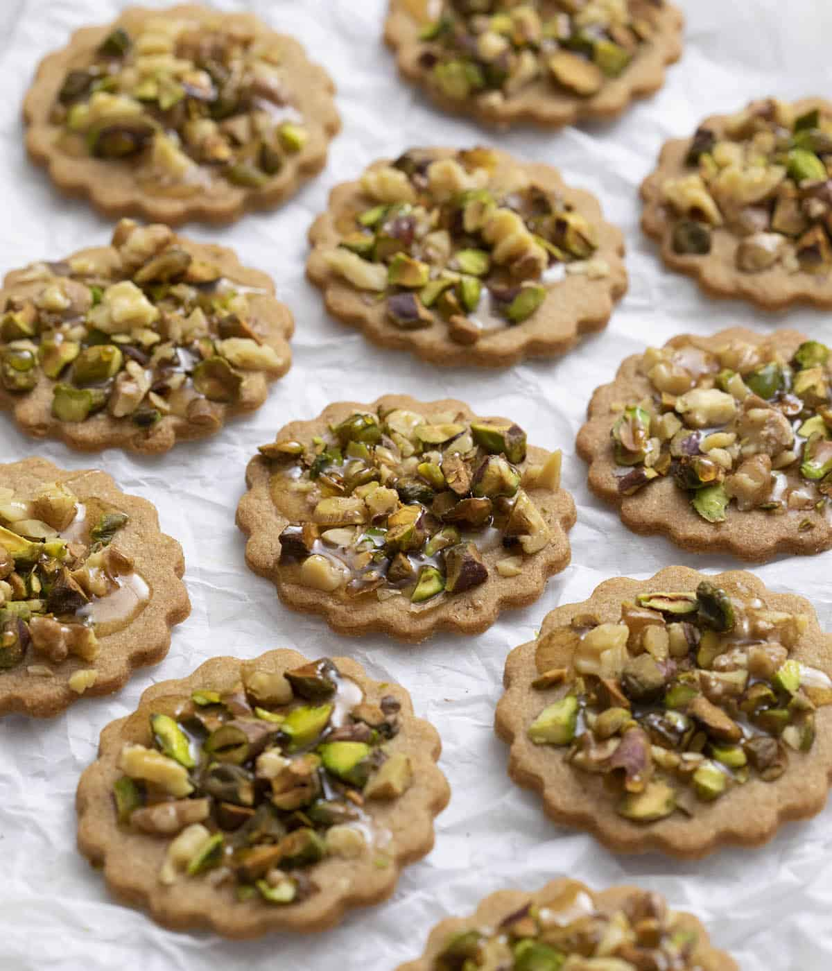 A group of baklava cookies on parchment paper.