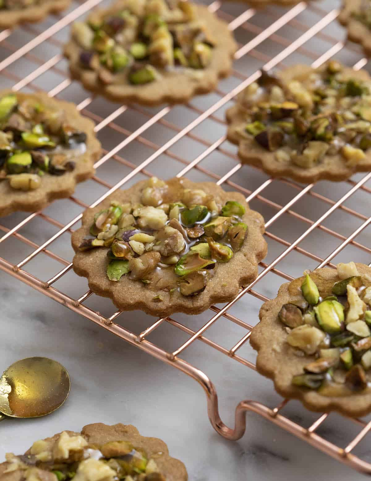 baklava cookies fresh out of the oven on a copper cooling rack.