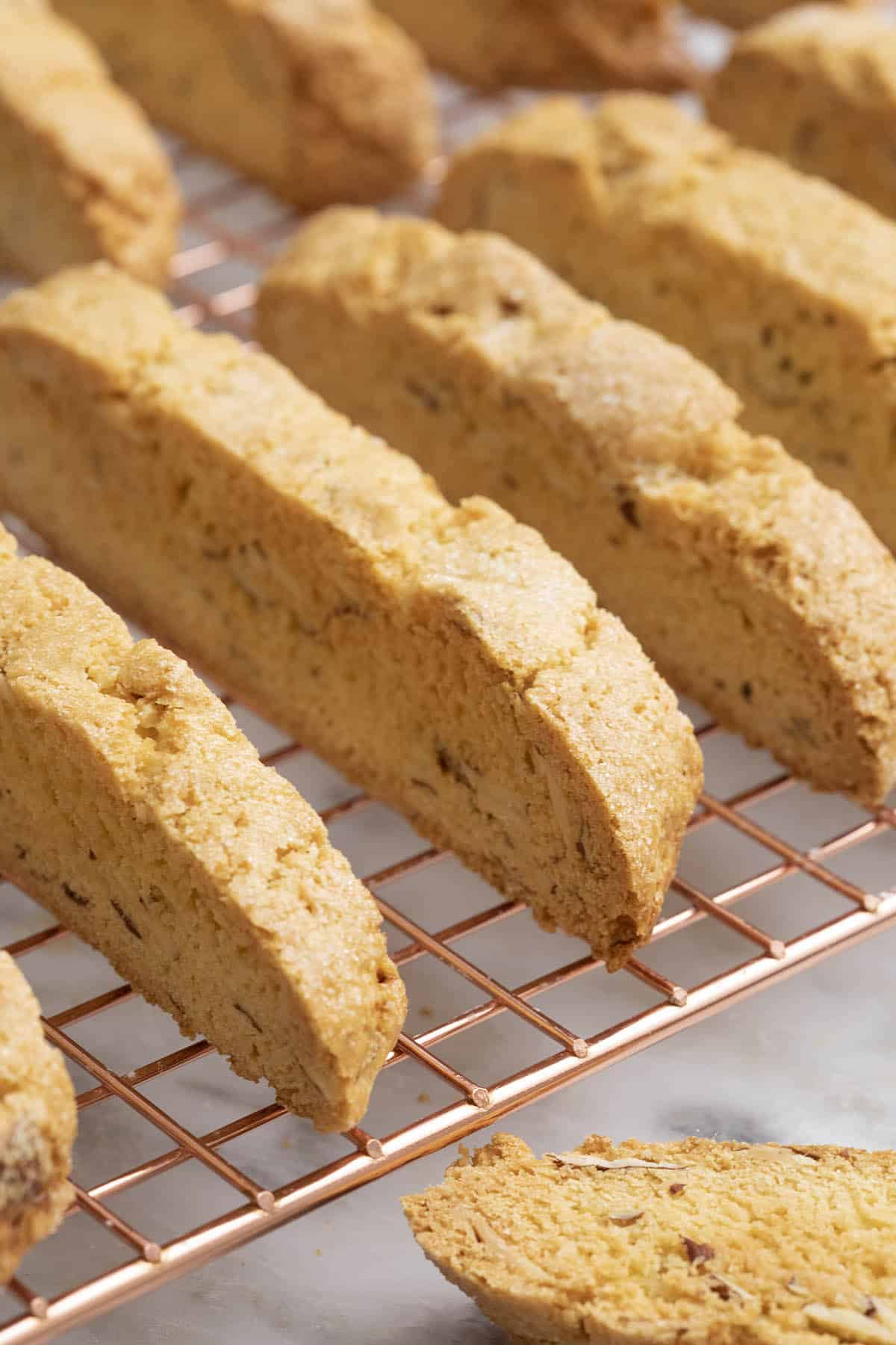 Freshly baked biscotti lined up on a copper cooling rack.