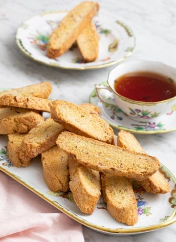 A group of delicious almond biscotti on a porcelain serving tray next to a teacup.