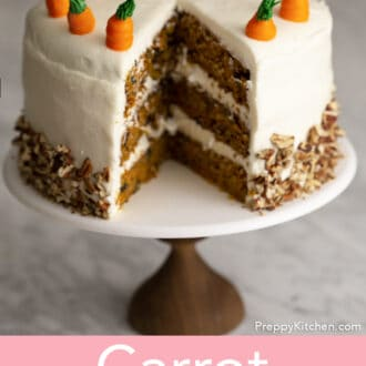 A big three layer carrot cake with a piece cut out.