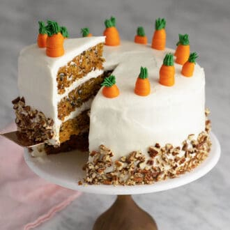 A delicious carrot cake getting cut and served from a cake stand.
