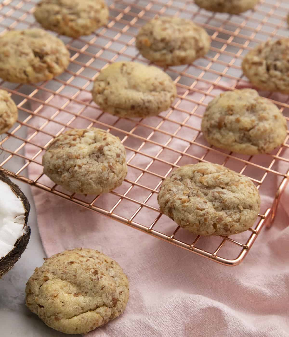 Coconut cookies fresh out of the oven on a copper rack.