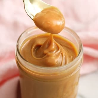 Silky dulce de leche getting spooned out of a glass jar.