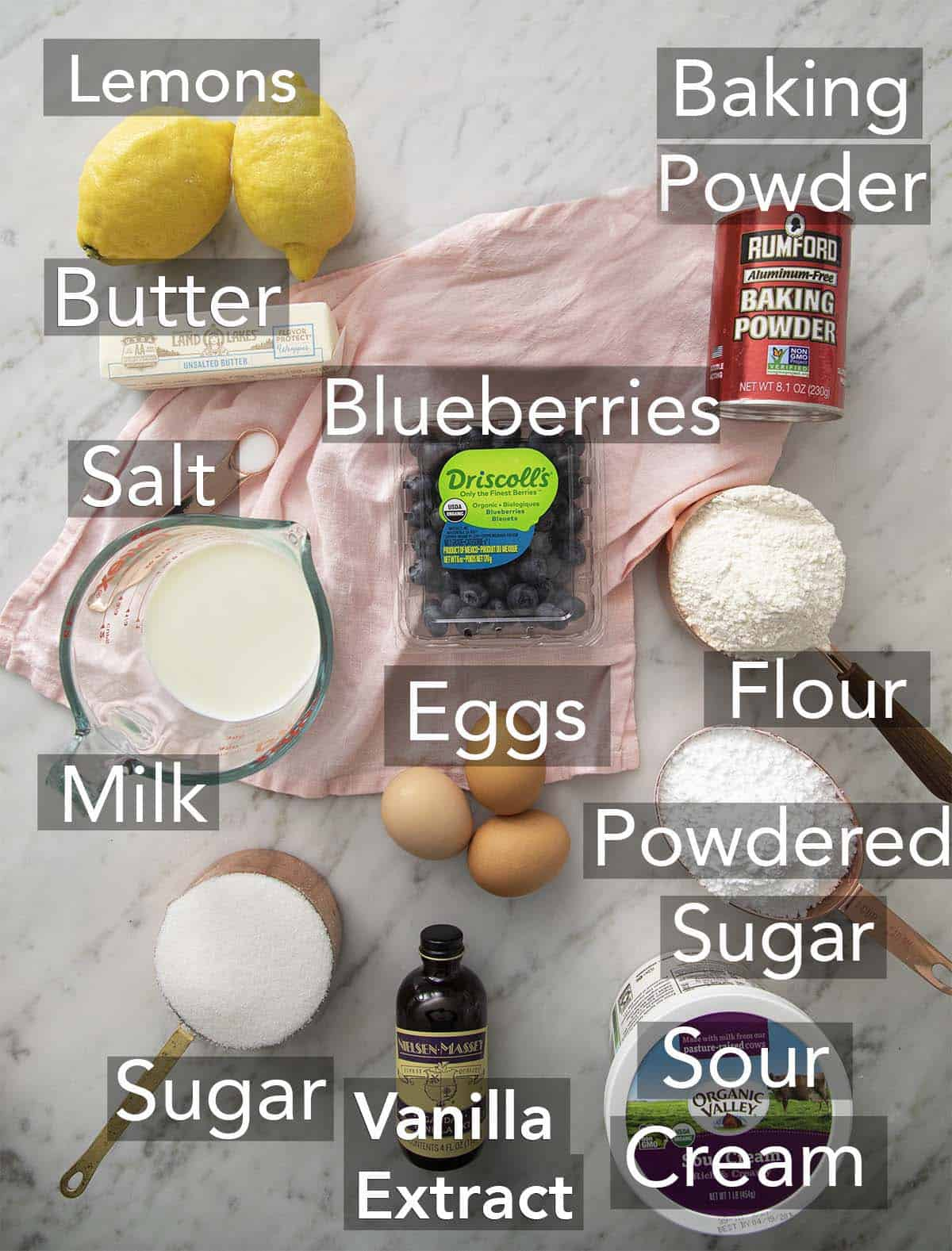 The ingredients for lemon blueberry cake on a marble surface.