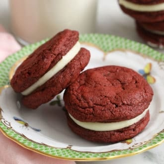 Two red velvet cookies next to a glass of milk.