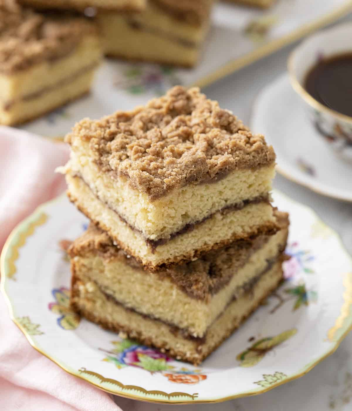 Two pieces of coffee cake with streusel topping on a plate.