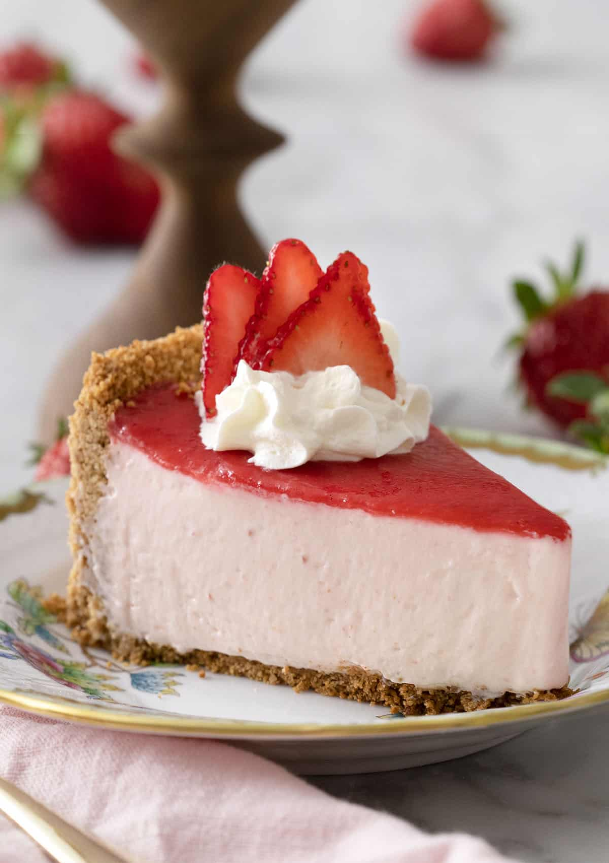 A piece of no bake strawberry cheesecake topped with a pink reduction and whipped cream on a porcelain plate.