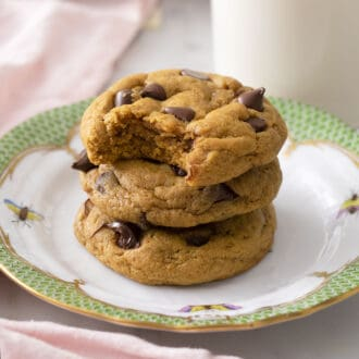 A stack of three delicious pumpkin chocolate chip cookies on a plate.