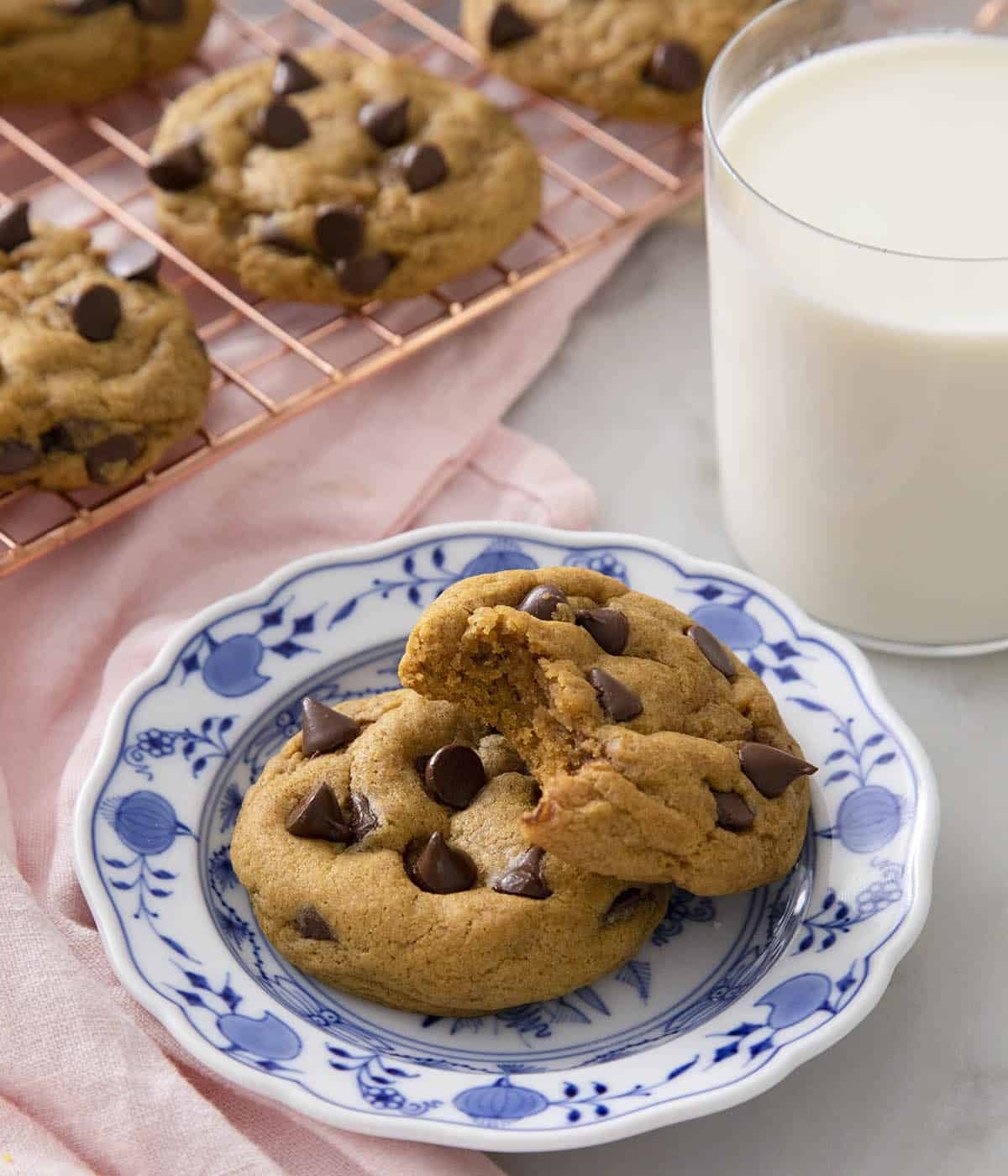 Two Pumpkin chocolate chip cookies on a blue and white plate next to a glass of milk.