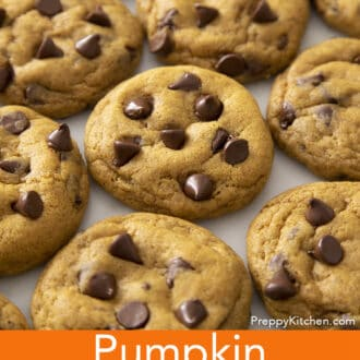 A group orf Pumpkin chocolate chip cookies next to each other on a marble counter.
