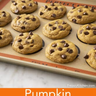 Pumpkin chocolate chip cookies on a silicone lined backing sheet.