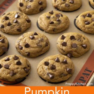 Freshly made pumpkin chocolate chip cookies on a baking sheet.