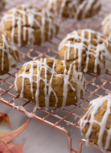 Pumpkin cookies on a copper cooling rack.