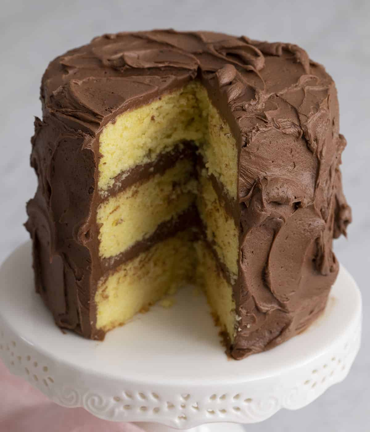 A three layer yellow cake with a piece cut out.