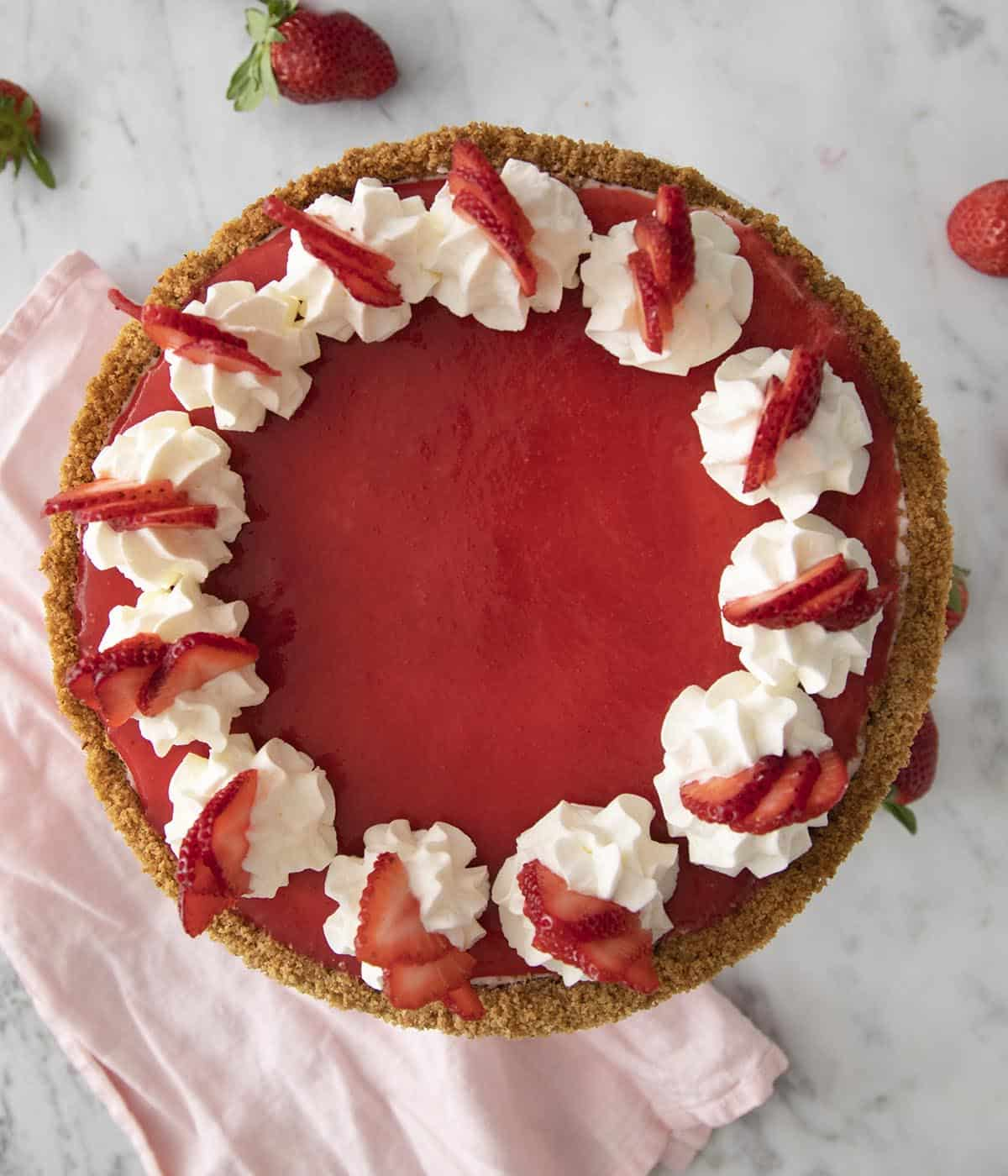 A top-down view of a beautiful no bake strawberry cheesecake with a ring of whipped cream dollops and strawberry slices on top.