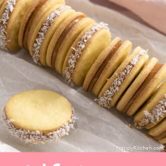 Alfajores coookies arranger on white parchment paper.