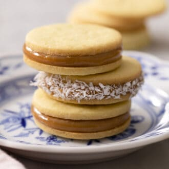 A stake of three alfajores on a blue and white plate.