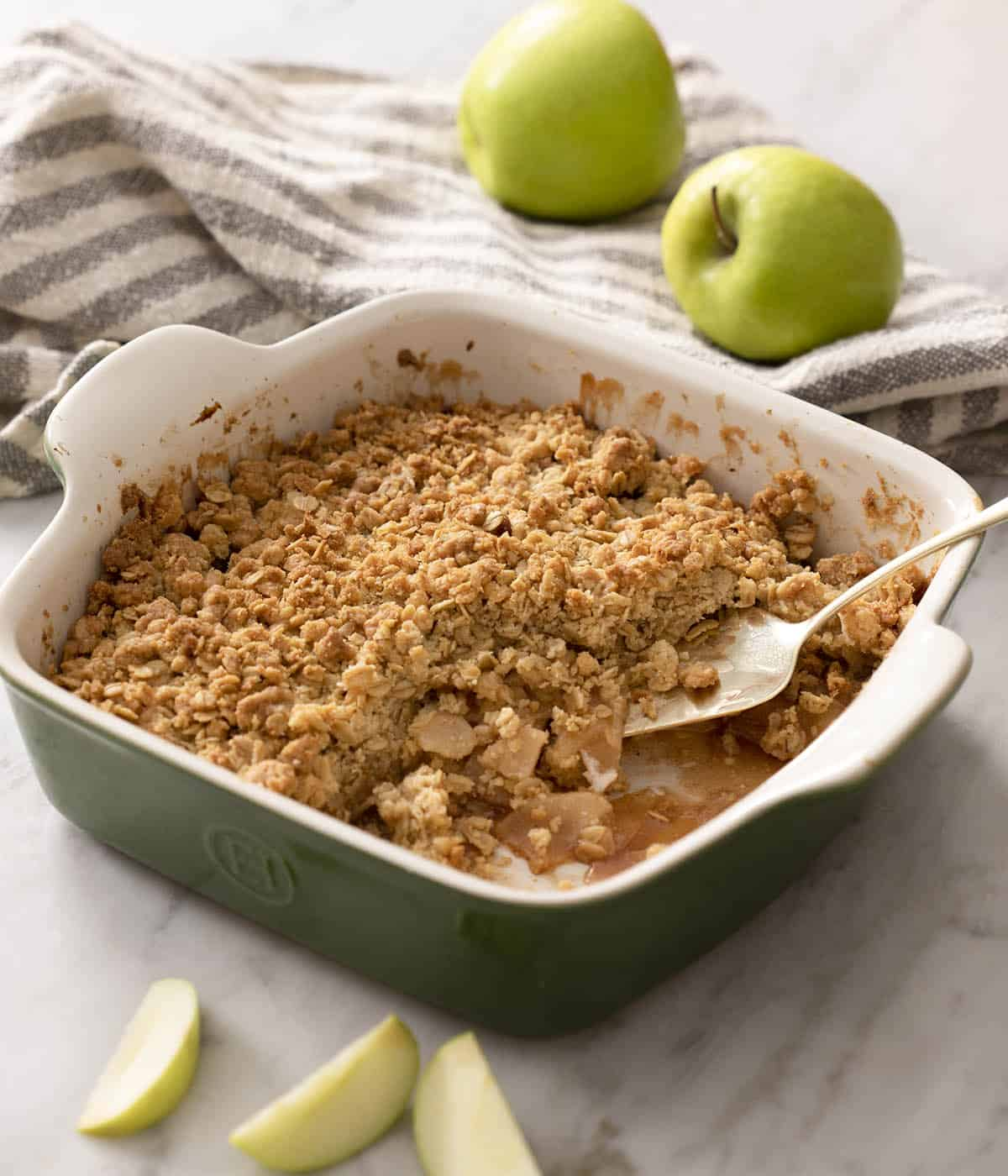 A baking dish of apple crisp on a marble counter.