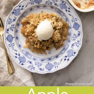 An apple crisp topped with a scoop of vanilla ice cream.