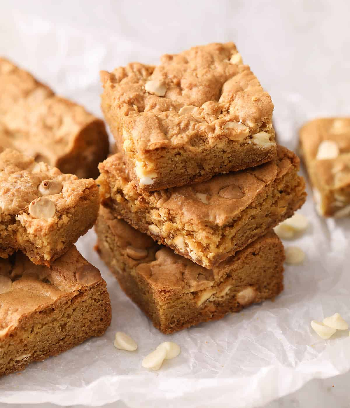 A group of blondies stacked on white parchment paper.