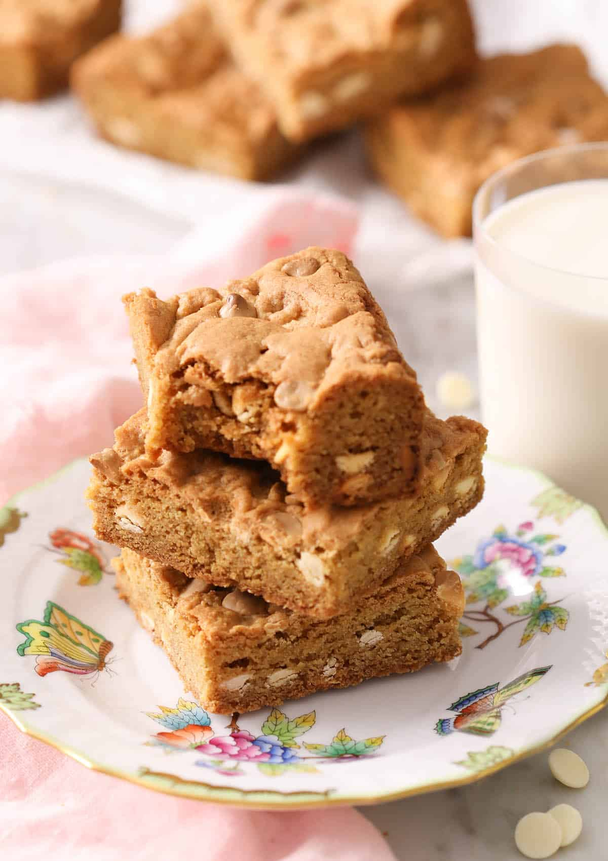 A group of blondies with white chocolate chips on a plate.