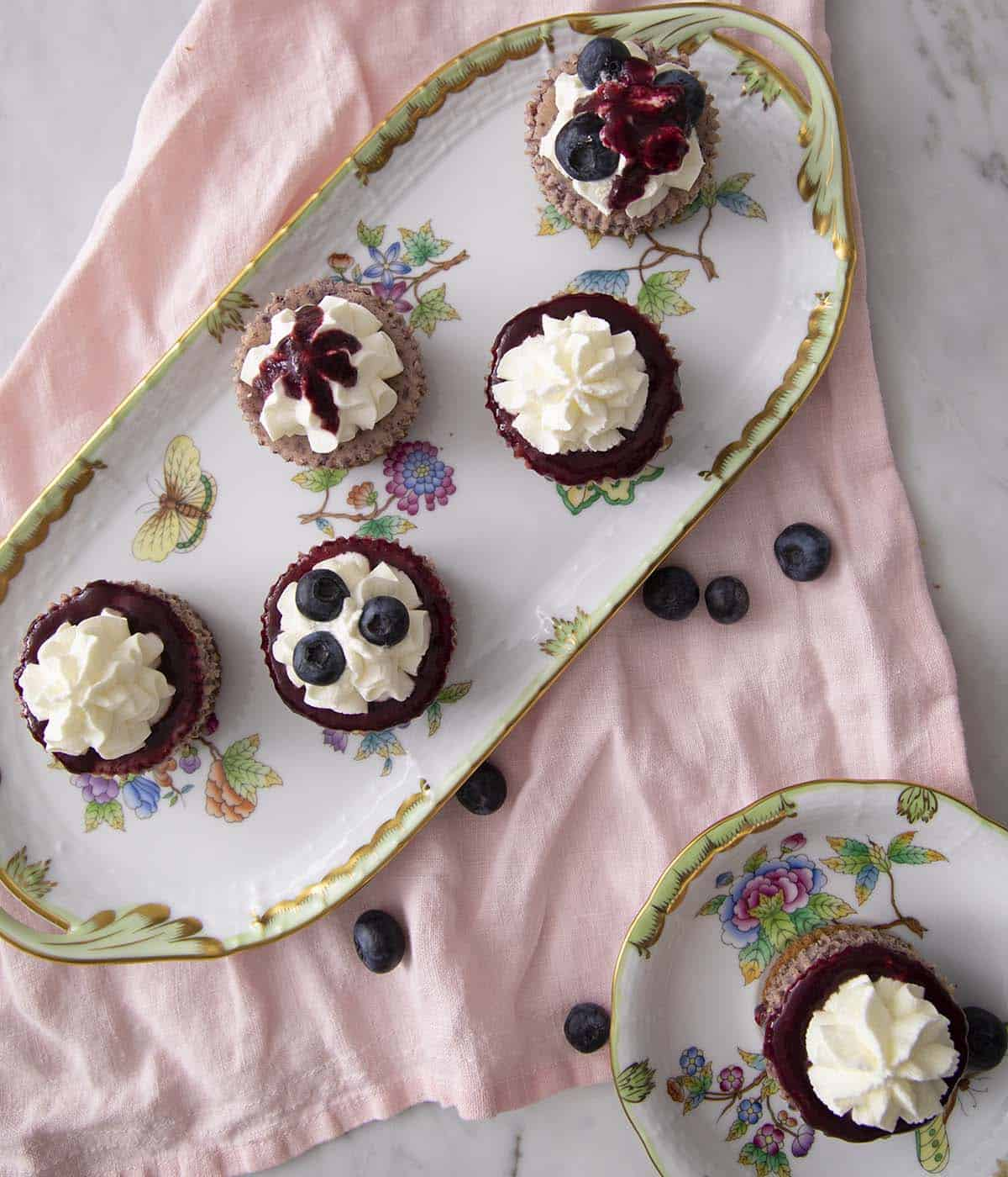 Porcelain dished with Blueberry mini cheesecakes decorated in different ways.