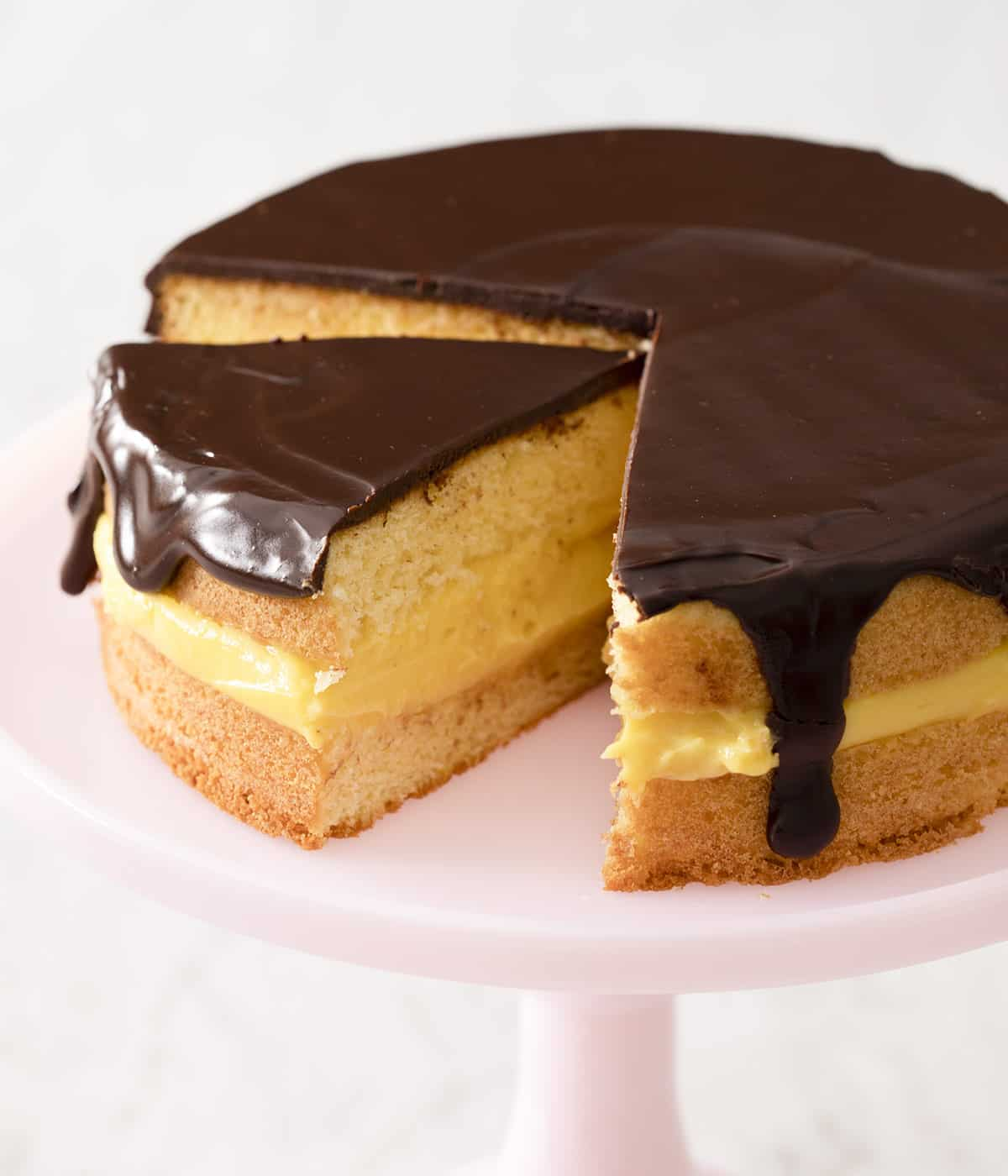 Boston cream pie with some pieces cut out on a cake stand.