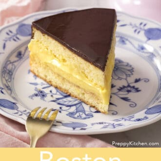 Boston cream pie next to a golden fork.