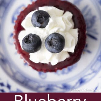 A top down photo of a blueberry mini cheesecake topped with a reduction and whipped cream on a plate.
