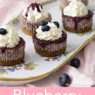 A group of Mini Blueberry Cheesecakes on a porcelain serving tray.