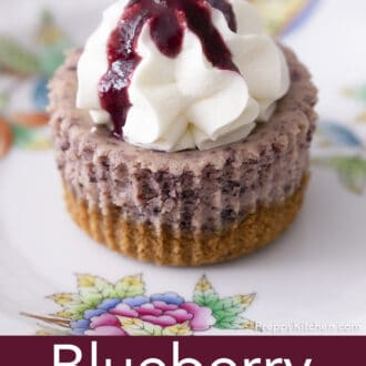 A mini blueberry cheesecake topped with whipped cream on a plate.
