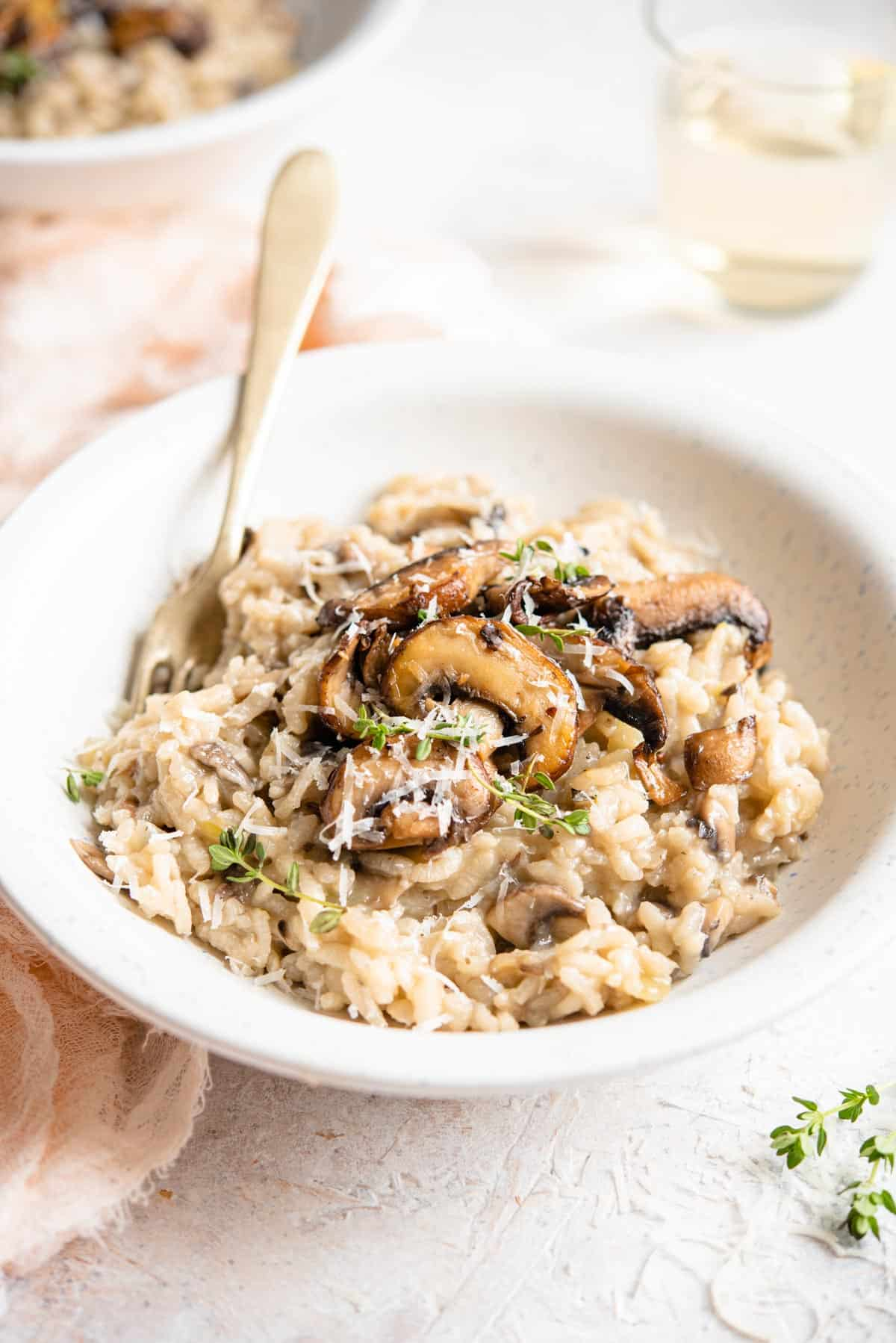 A side shot of mushroom risotto in a bowl topped with parmesan and thyme