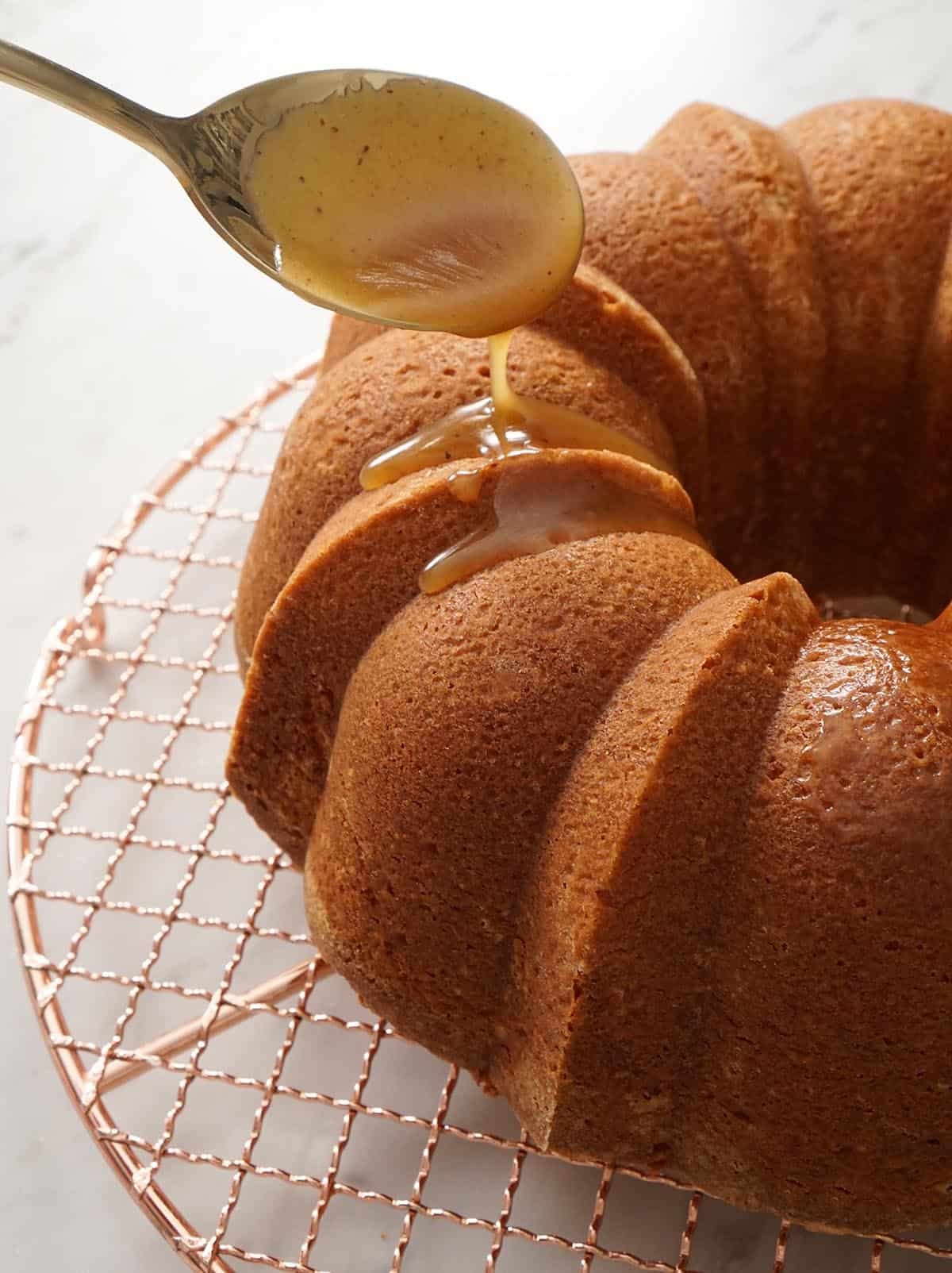 Rum sauce getting spooned onto a bundt cake.