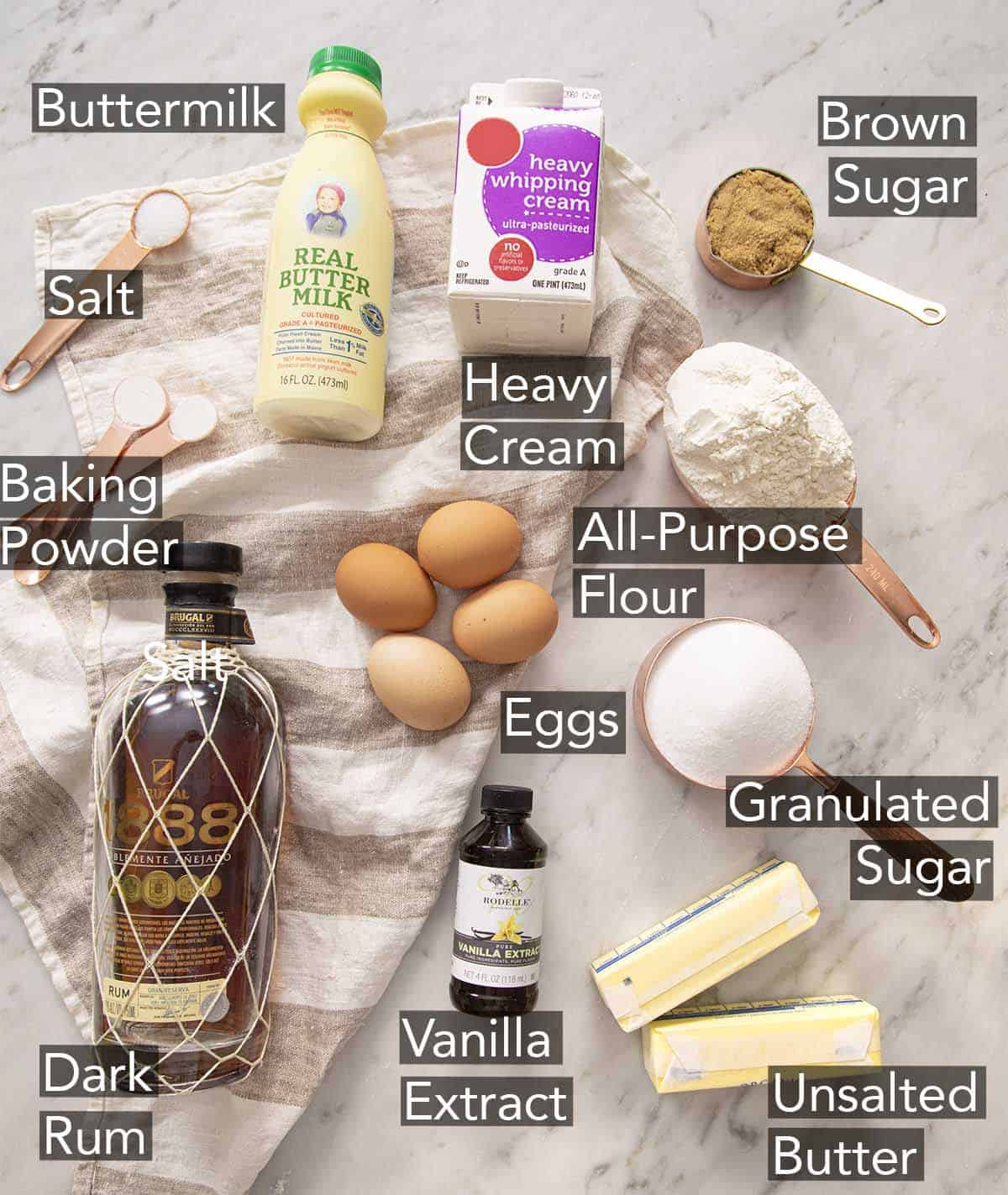 Ingredients to make a rum cake on a marble counter.