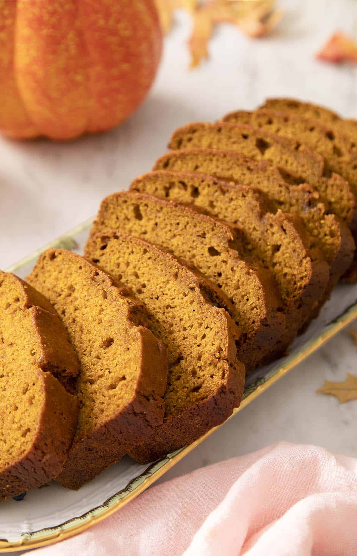 Sliced pumpkin bread on a porcelain serving plate.