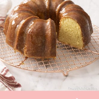 A rum cake with a piece cut out on a wire rack.