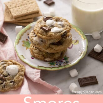 A stack of smores cookies next to a glass of milk.