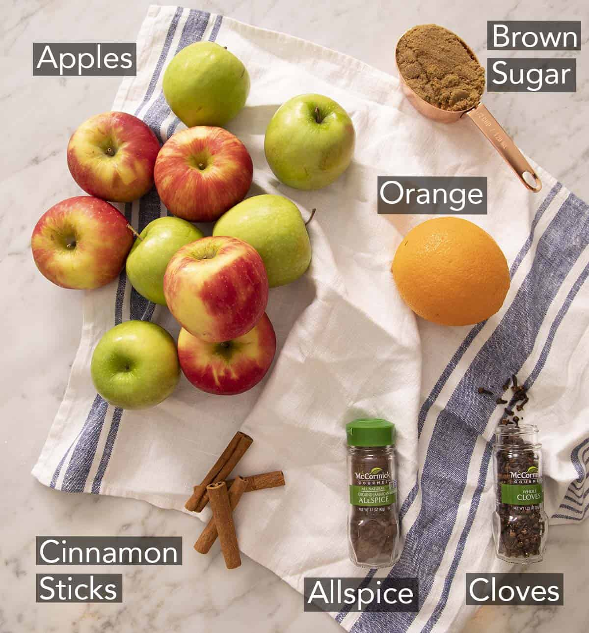 Ingredients to make apple cider on a marble counter.