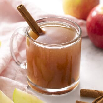 A glass mug of apple cider with a cinnamon stick inside.