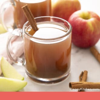Amber colored apple cider in glass mugs.