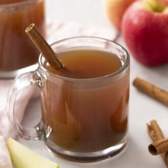 Apple cider glasses next to apples and cinnamon.